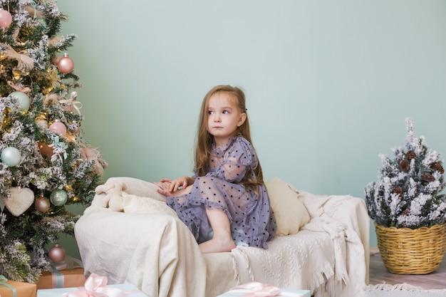 Uma menina bonitinha em um lindo vestido está brincando perto da árvore de natal.