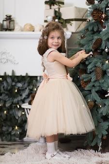Uma menina bonitinha em um vestido bege exuberante pendura cones na árvore de natal que está em pé na casa. conto de natal, infância feliz.