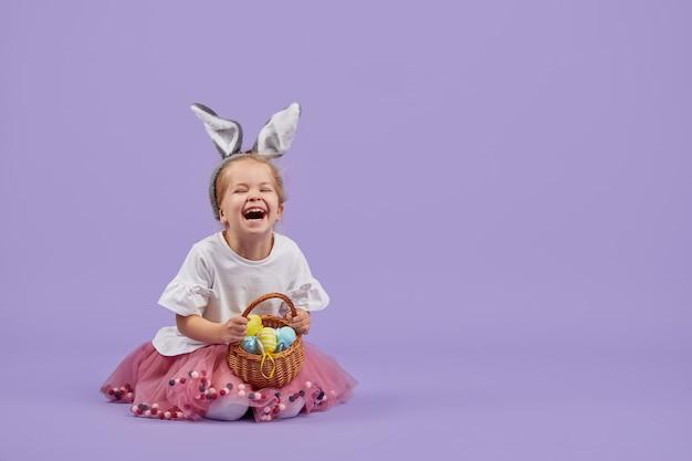 Uma menina bonitinha em uma fantasia de coelhinho da páscoa senta-se perto de um ovo enorme e segura uma cesta com pequenos ovos coloridos. espaço roxo studio. copie o espaço para texto