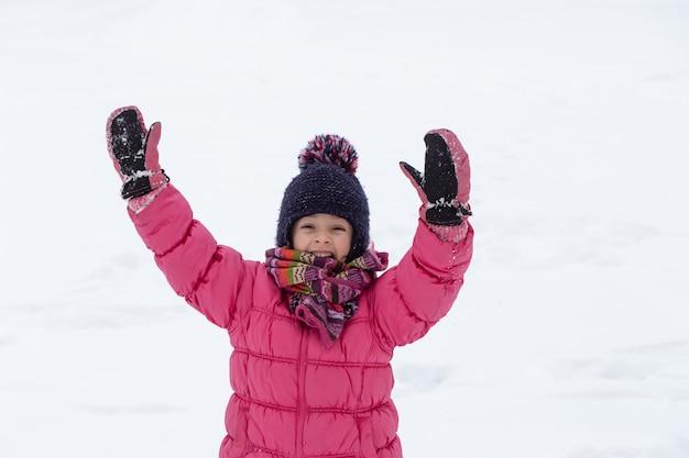 Uma menina bonitinha em uma jaqueta rosa e um chapéu está brincando na neve. conceito de entretenimento infantil de inverno.