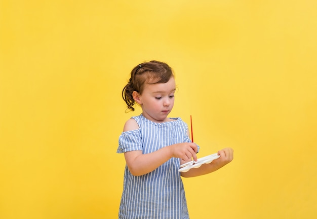 Uma menina bonitinha está desenhando com um pincel com um chicote nas mãos dela sobre um fundo amarelo com espaço para texto.