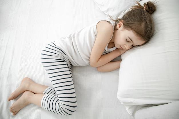 Uma menina bonitinha está dormindo em uma cama branca. conceito de desenvolvimento infantil e sono.