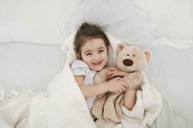 Uma menina bonitinha está dormindo em uma cama com um brinquedo de ursinho de pelúcia.