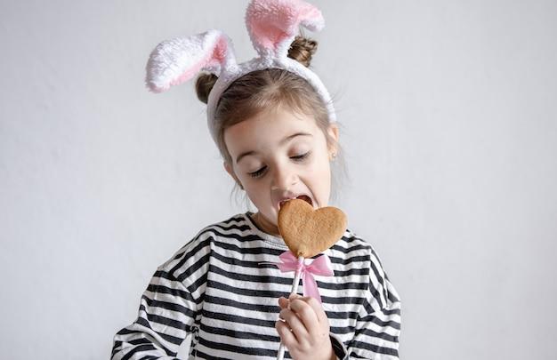 Uma menina bonitinha está mordendo um pão de mel de páscoa em um palito e com orelhas de coelho decorativas na cabeça.