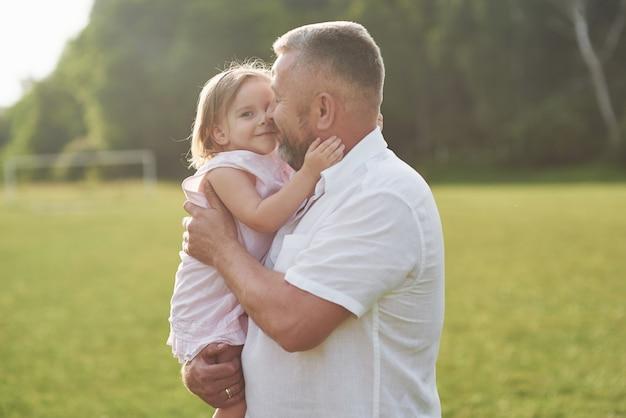 Uma menina bonitinha está passando tempo com seu amado avô no parque
