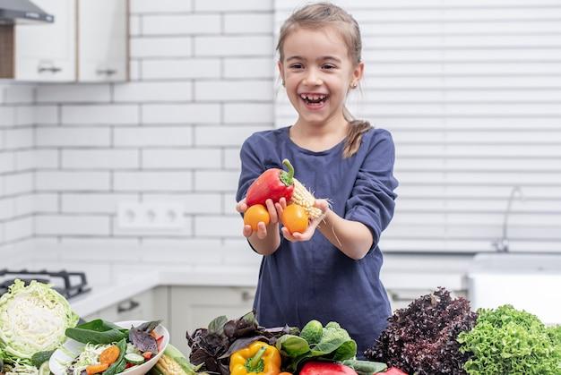 Uma menina bonitinha está segurando legumes frescos enquanto prepara um espaço de cópia de salada.