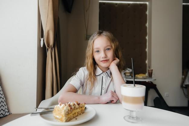 Uma menina bonitinha está sentado em um café e olhando para um bolo e cacau close-up. dieta e nutrição adequada.