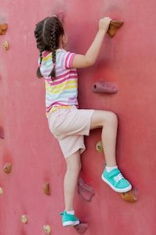 Uma menina bonitinha está subindo uma grande parede artificial.