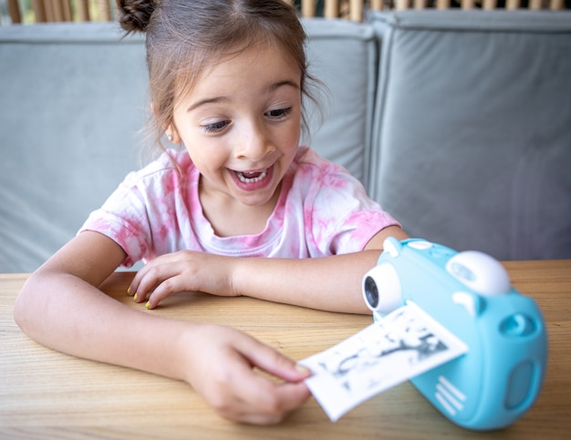 Uma menina bonitinha olha para a câmera de brinquedo azul de seus filhos para impressão instantânea de fotos.