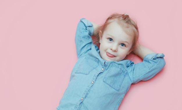 Uma menina branca bonito está encontrando-se em um fundo cor-de-rosa com suas mãos atrás de sua cabeça.
