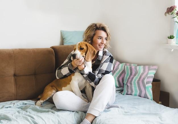 Uma menina brinca com seu amado cachorro em casa sentada em um sofá aconchegante
