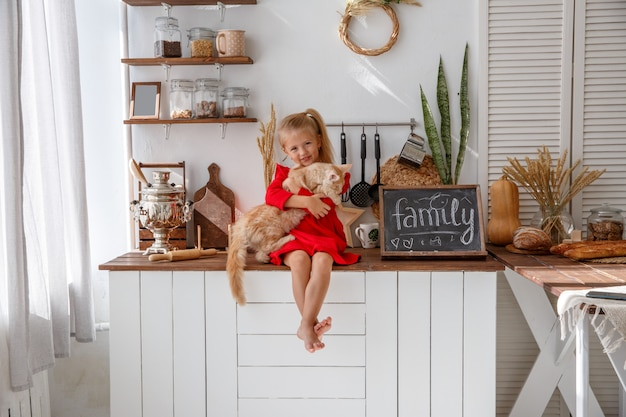 Uma menina brinca com um gatinho na cozinha da casa. o conceito de família humana e animal de estimação