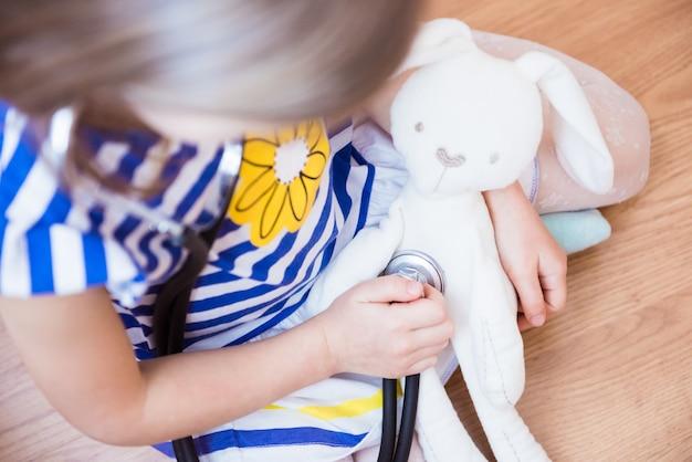Uma menina brinca de médico com seu coelho branco