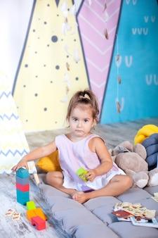 Uma menina brinca no chão com cubos de madeira coloridos e constrói uma torre