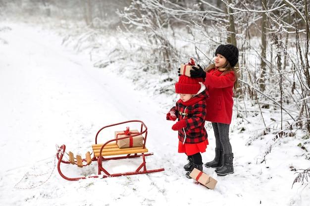 Uma menina, brincando, coloca presentes de natal na cabeça da irmã