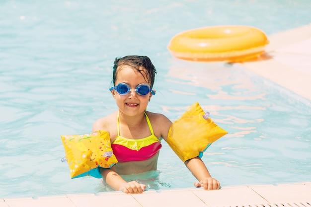 Uma menina brincando na piscina de verão