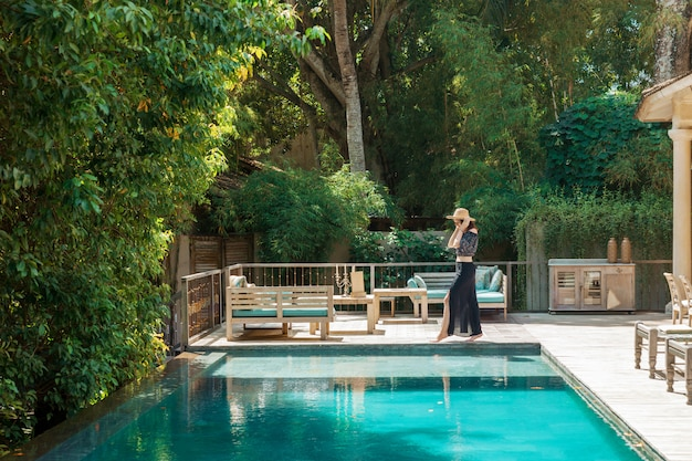 Uma menina caminha ao longo da piscina privada de um hotel de luxo em bali