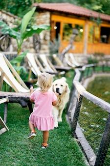 Uma menina caminha até o cachorro no gramado verde perto do lago