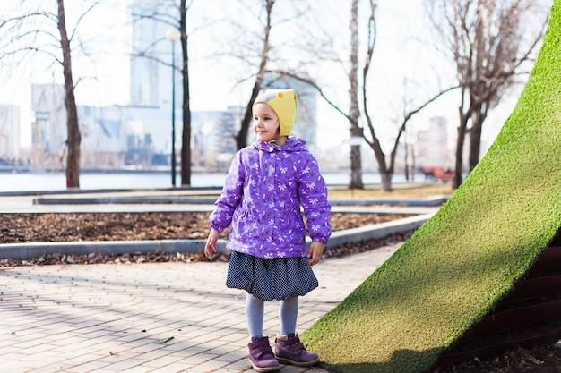 Uma menina caminha na rua, na cidade, anda de scooter, caminha com sua família, infância, alegria, primavera