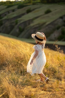 Uma menina caminha no campo com um chapéu.