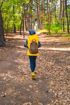 Uma menina caminha pela floresta de primavera