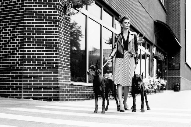 Uma menina caminha pela rua na cidade ao longo do edifício com dois dobermans na coleira