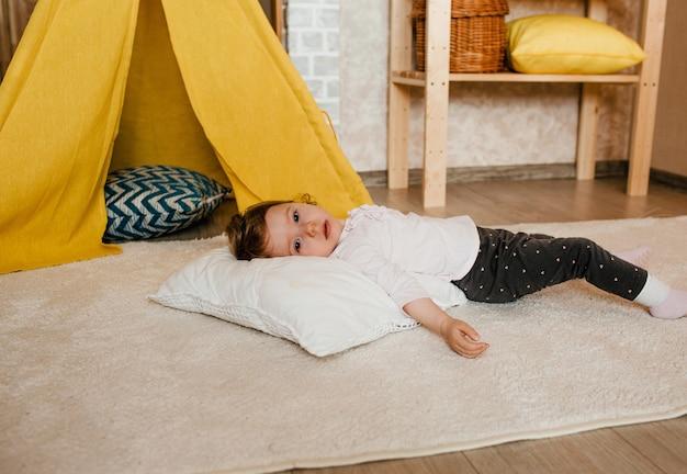 Uma menina cansada está descansando deitada no chão. cabana amarela