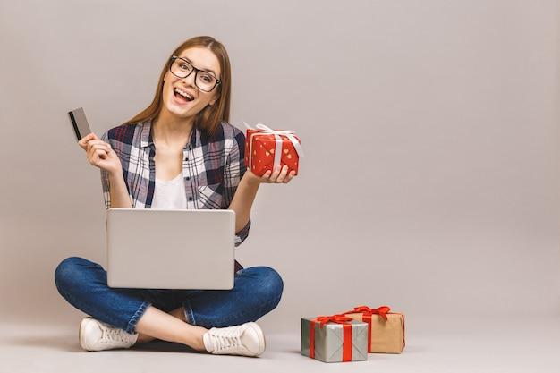 Uma menina casual animada segurando computador portátil e cartão de crédito enquanto está sentado no chão com uma pilha de caixas de presente