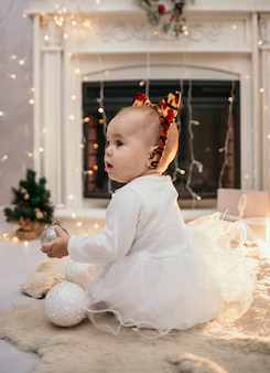 Uma menina caucasiana com um vestido fofo e uma bandana com orelhas de tigre sentada em um tapete de pele em um quarto com decorações de ano novo