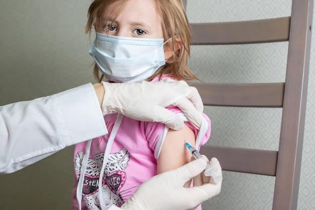 Uma menina caucasiana de 5 anos com máscara médica recebe vacina contra infecção por coronavírus
