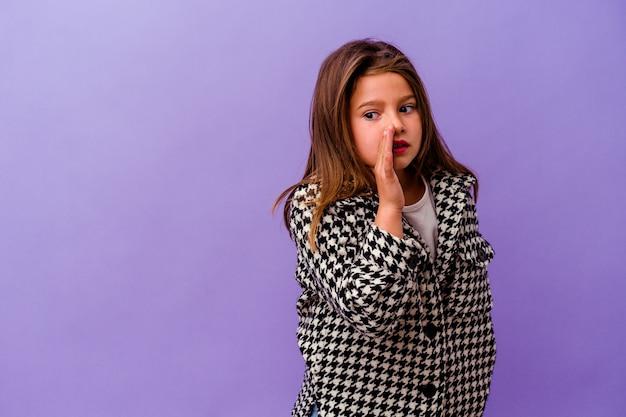 Uma menina caucasiana isolada na parede roxa está contando uma notícia secreta sobre a travagem e olhando para o lado