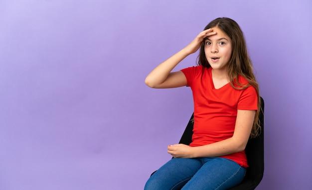 Uma menina caucasiana sentada em uma cadeira isolada em um fundo roxo percebeu algo e pretende a solução