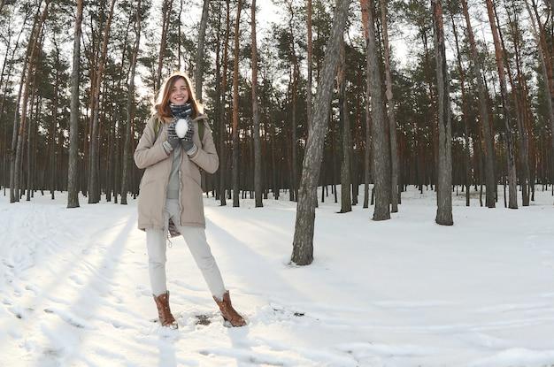 Uma menina caucasiano nova e alegre em um revestimento marrom prende um snowball em uma floresta snow-covered no inverno. olho de peixe foto