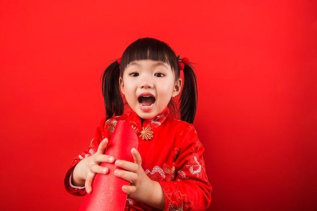 Uma menina chinesa celebra o ano novo chinês com um envelope vermelho
