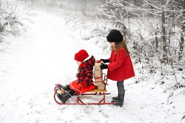 Uma menina coloca presentes com uma fita vermelha em um trenó onde sua irmã está sentada