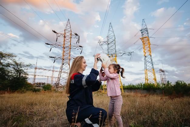 Uma menina coloca um capacete para sua mãe para um trabalhador de engenharia