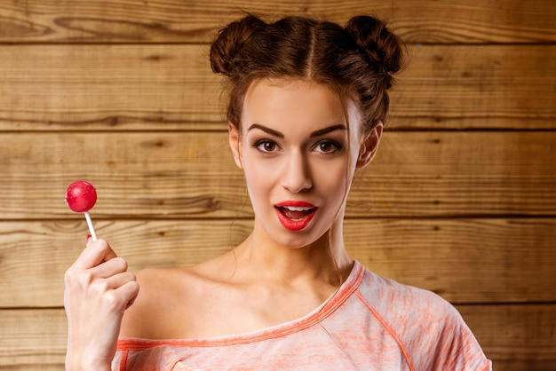 Uma menina com a boca aberta está de pé com um pirulito.