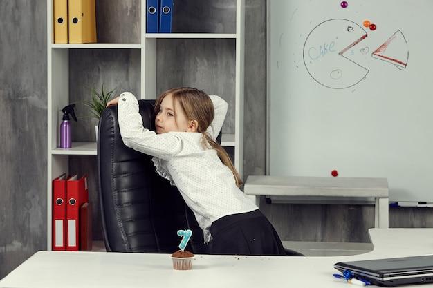 Uma menina com a imagem de um trabalhador de escritório está ociosa enquanto trabalha