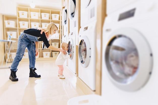 Uma menina com a mãe joga roupas na máquina de lavar roupa