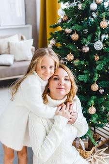 Uma menina com a mãe perto da árvore de natal, o interior decorado para o ano novo e o natal, a família e a alegria, as tradições