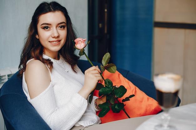Uma menina com a rosa e sobremesa no café