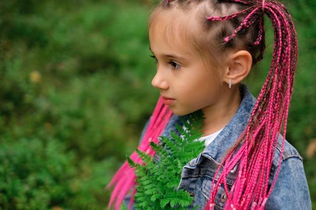 Uma menina com afropigtails presos em um rabo segura uma folha de samambaia