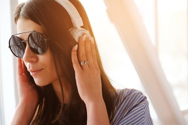 Uma menina com cabelo escuro em fones de ouvido, ouvindo música