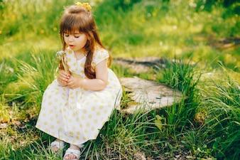 Uma menina com cabelo longo bonito e em um vestido amarelo está jogando no verão