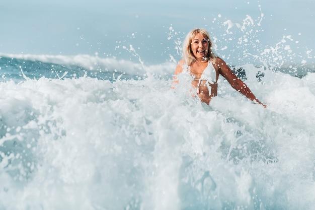 Uma menina com cabelos escuros molhados está de pé até a cintura, de costas para a câmera, na espuma branca da água do mar, ao redor de uma onda com respingos e gotas de água voando para longe.