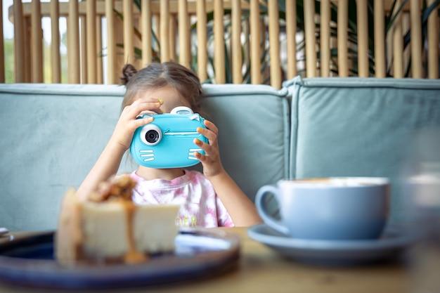 Uma menina com câmera digital de brinquedo para crianças para impressão instantânea de fotos.