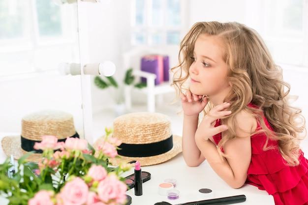 Uma menina com cosméticos, sentado perto do espelho.