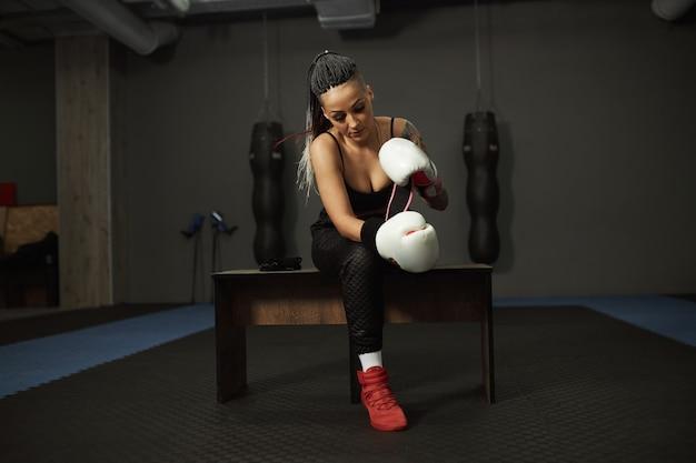 Uma menina com deficiência está envolvida no ginásio. uma mulher com uma perna treina com um treinador de boxe, ela aprende a lutar
