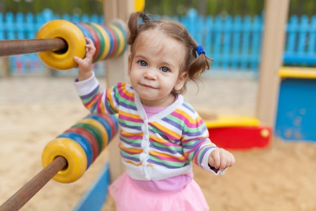 Uma menina com duas caudas brincando na caixa de areia no playground