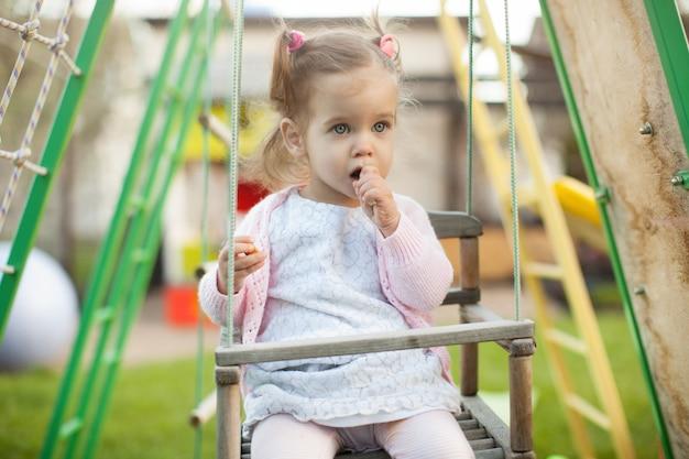 Uma menina com duas caudas brincando no playground